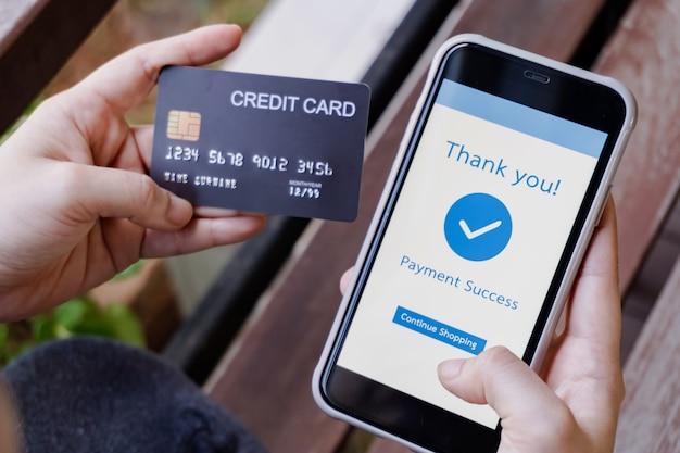 オンラインショッピング、モバイル決済。クレジットカードを保持し、オンライン決済にスマートフォンを使用して女性の手