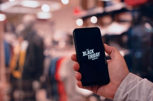 ブラックフライデーのオンラインショッピング。ファッショナブルな衣料品店を背景に、男性がスマートフォンを手に持っています。