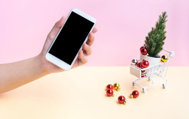 Интернет-магазины зимой, рождество с молодой женщиной, показывающей смартфон
