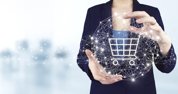 온라인 쇼핑 또는 인터넷 상점 개념. 밝은 배경이 흐릿한 가상 홀로그램 카트 아이콘을 들고 있는 두 손. 인터넷 장바구니 웹 스토어 온라인 전자 상거래 개념을 구매합니다.