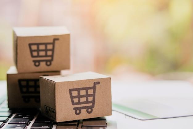 オンラインショッピング-ショッピングカートのロゴとラップトップキーボードのクレジットカードが入った紙パックまたは小包。オンラインweb上のショッピングサービスおよび宅配便を提供しています。