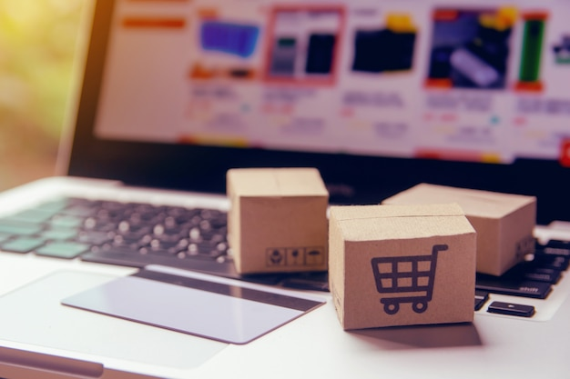 온라인 쇼핑-쇼핑 카트 로고와 노트북 키보드에 신용 카드가있는 종이 상자 또는 소포. 온라인 웹 쇼핑 서비스 및 택배를 제공합니다.