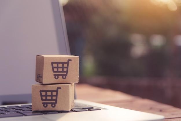 온라인 쇼핑 : 랩탑 키보드에 장바구니 로고가있는 종이 상자 또는 소포. 온라인 웹 쇼핑 서비스 및 택배를 제공합니다.