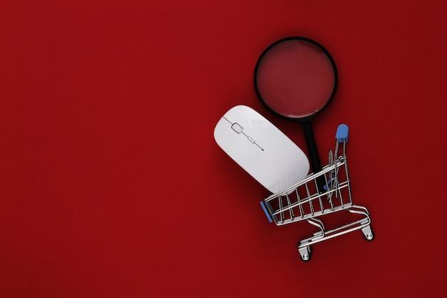 オンラインショッピング。赤の背景に時計付きのpcマウスとミニショッピングトロリー。上面図。フラットレイ
