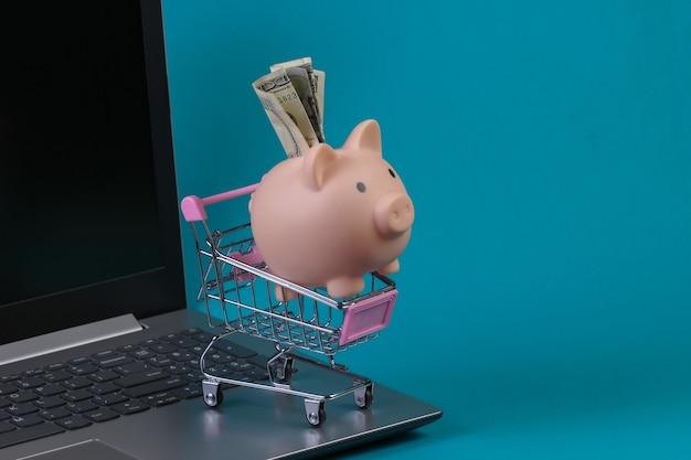온라인 쇼핑. 달러 bil 돼지 저금통, 노트북 키보드에 미니 슈퍼마켓 트롤리. 파란색 벽.