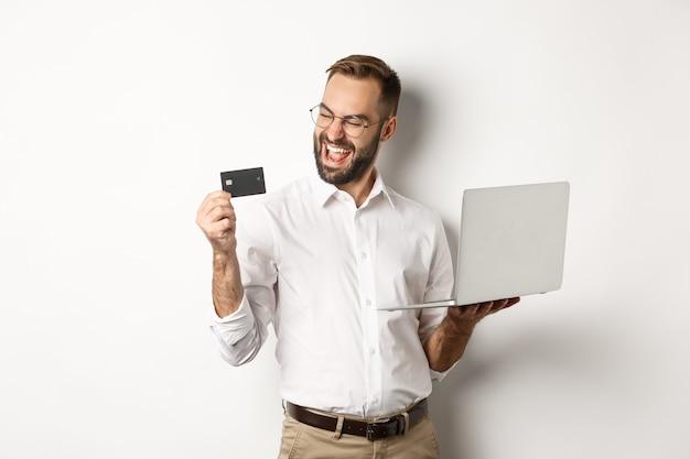 Онлайн шоппинг. удовлетворенный красавец, глядя на кредитную карту после оформления заказа в интернете, используя ноутбук, стоя на белом фоне.