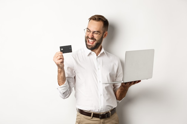 Покупки в интернет магазине. довольный красавец смотрит на кредитную карту после оформления заказа в интернете, используя ноутбук, стоя