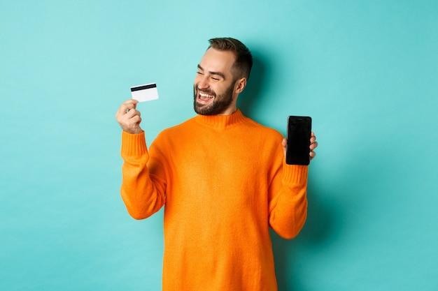 オンラインショッピング。クレジットカードを使用してモバイル画面を表示し、満足しているように見える満足している男性
