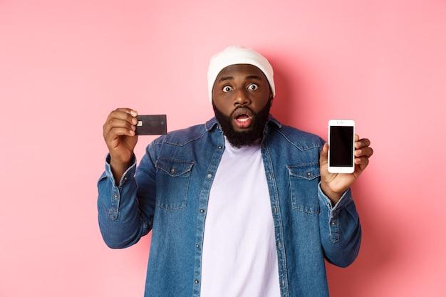 オンラインショッピング。ピンクの背景の上に立って、カメラを見つめ、携帯電話の画面とクレジットカードを見せて、ショックを受けて心配している黒人男性。