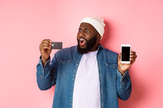 Online shopping. shocked black man showing mobile phone screen, looking startled at credit card, standing in hipster clothes against pink background.
