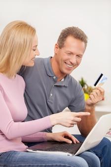 온라인 쇼핑. 측면 보기 쾌활한 성숙한 부부는 함께 노트북을 사용하고 신용 카드를 들고 있는 동안 웃고