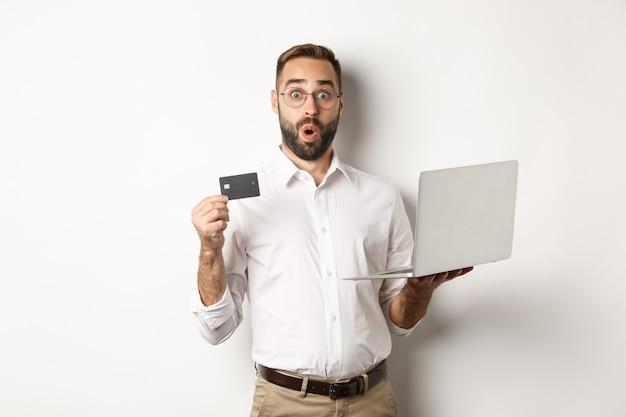 オンラインショッピング。ノートパソコンとクレジットカードを持って、インターネットストアを購入し、立っている驚きの男