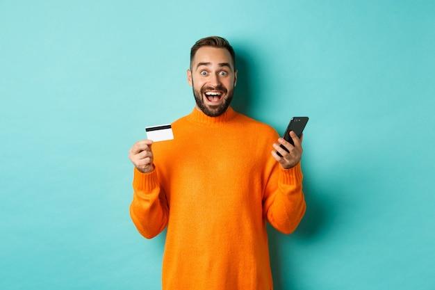 オンラインショッピング。携帯電話とクレジットカードを持って、インターネットストアで支払う驚いた男