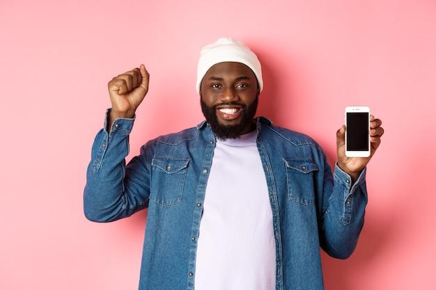Shopping online e concetto di tecnologia. allegro uomo nero che si rallegra e mostra lo schermo mobile, alzando la mano soddisfatto, trionfando stando in piedi su sfondo rosa