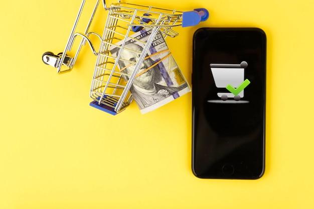 Интернет-магазин, телефон и концепция тележки покупателя с рулоном стодолларовых купюр на желтом фоне. скопируйте пространство.