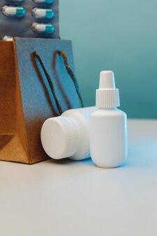 Тема интернет-магазинов. бумажные пакеты с медицинскими белыми контейнерами и таблетками на синем фоне. вертикальное изображение.