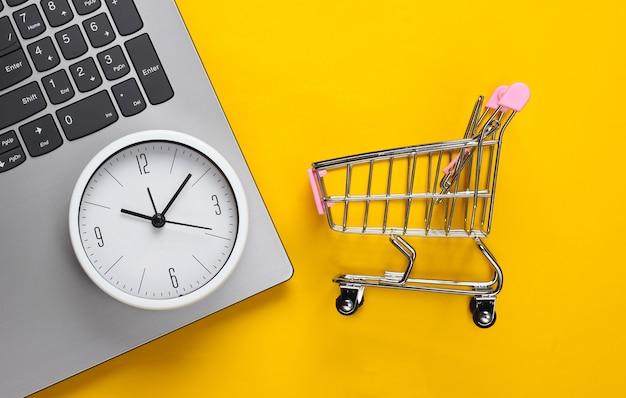オンラインショッピングの時間。黄色の背景に時計とスーパーマーケットのトロリーとコンピューターのキーボード。上面図