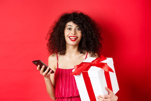 Online shopping and valentines day. beautiful young woman holding smartphone and lovers gift, looking surprised and happy at camera, red background.