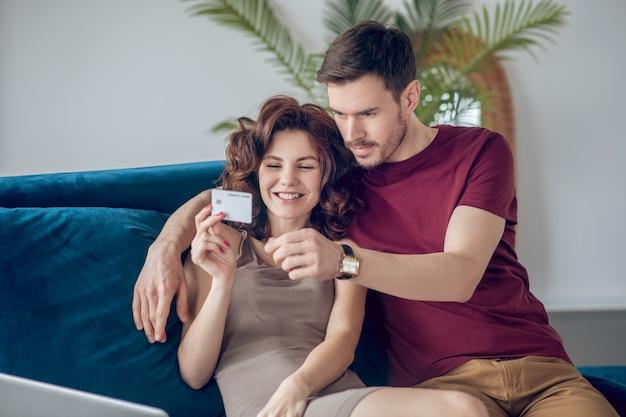 온라인 쇼핑. 젊은 커플 소파에 siting 및 온라인 제품 선택