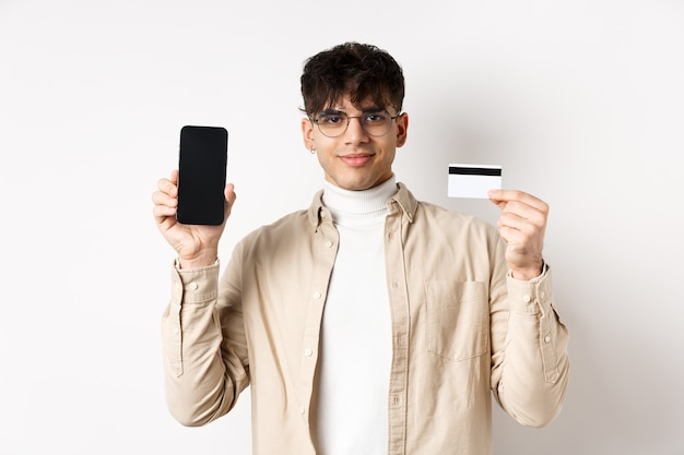 Online shopping young modern guy showing plastic credit card and empty smartphone screen demonstrate...