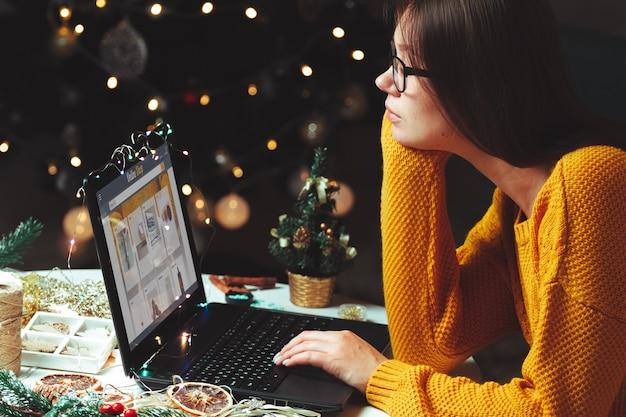 Интернет-магазины молодая женщина с ноутбуком на рождество