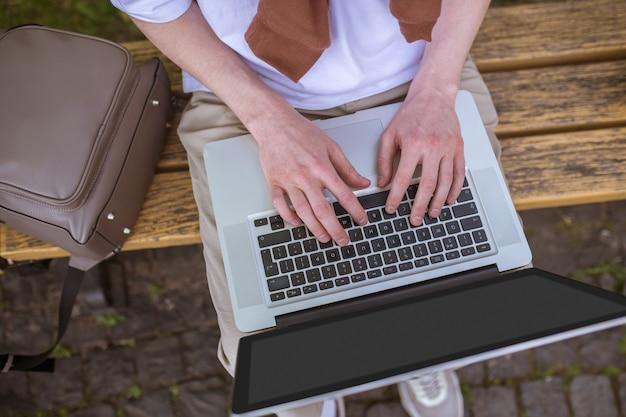 Онлайн. сидя на скамейке с ноутбуком и печатаю