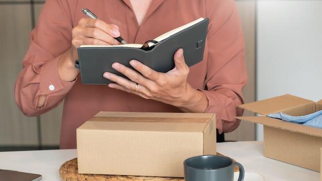 고객, 시작 및 온라인 비즈니스 개념을 제공하기 위해 제품을 준비하는 상점에서 일하는 온라인 소규모 기업가 상인.