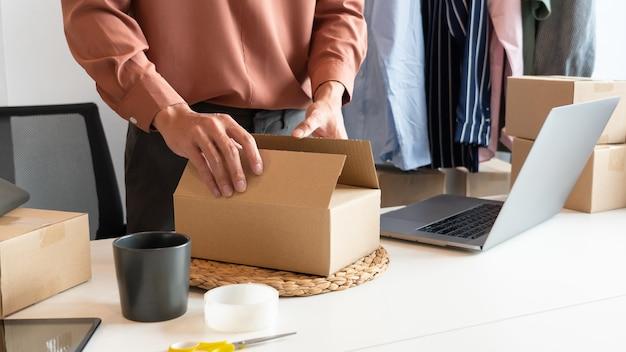 顧客に配達する製品を準備する店で働くオンライン中小企業の起業家商人