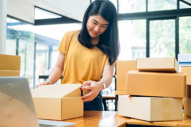 Интернет-владелец малого бизнеса. молодой начинающий предприниматель онлайн владелец малого бизнеса, работающий на дому, упаковка и доставка.