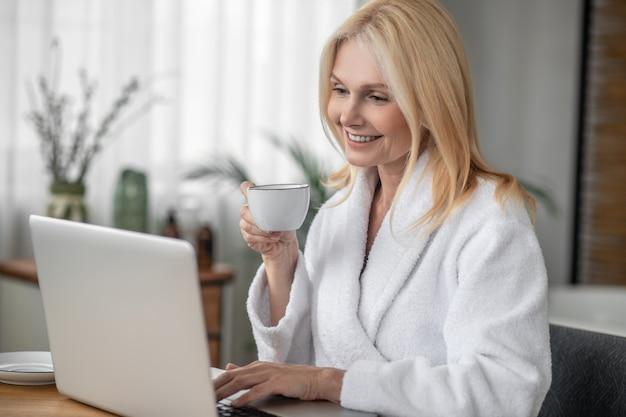 オンライン。コーヒーを飲んでオンラインで何かを見ている長髪の女性の笑顔