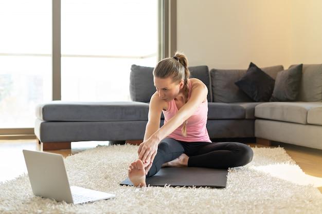 온라인 스포츠 피트니스 요가 훈련. 젊은 여자와 요가 매트에 연습을 하 고