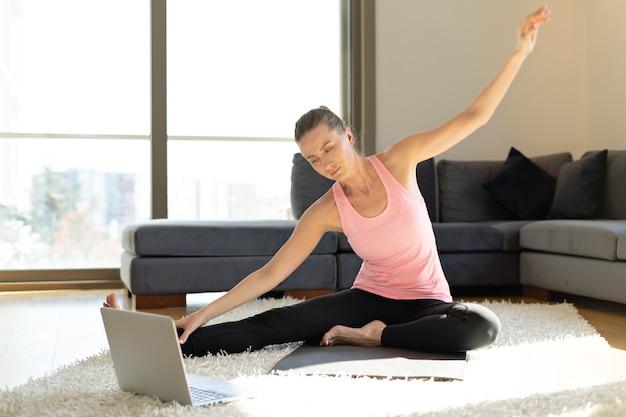 Онлайн спорт фитнес йога обучение. молодая женщина с ноутбуком