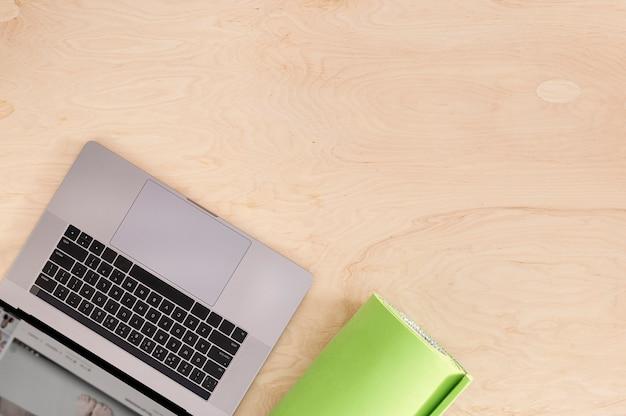 나무 바닥에 요가 매트와 온라인 스포츠 또는 교육 과정 개념 상위 뷰 노트북