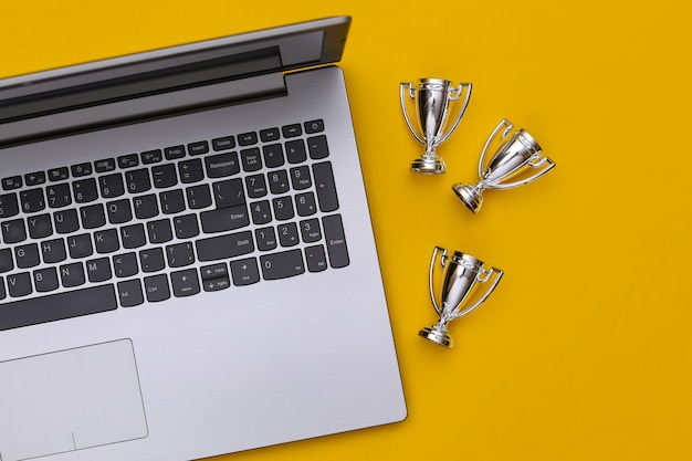 온라인 스포츠 베팅. 노란색 배경에 노트북 및 챔피언십 컵입니다. 평면도. 플랫 레이