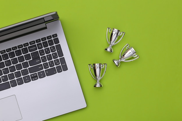 Online sports betting. laptop and championship cups on green background. top view. flat lay