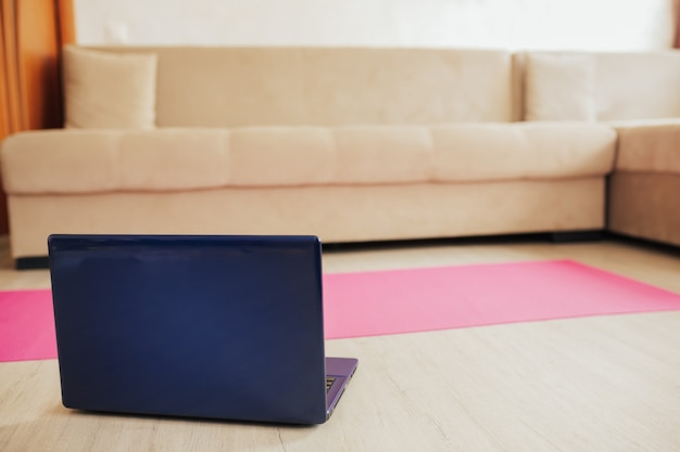 분홍색 요가 매트가있는 노트북에서 온라인 스포츠 또는 요가 교육
