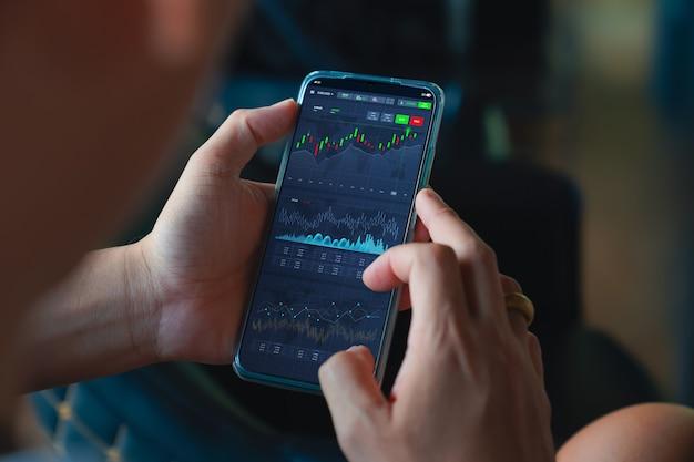 온라인 주식 거래 플랫폼 개념 남자는 투자를 구매하기 전에 휴대전화를 통해 온라인 시장에서 투자 계정 대시보드와 주가를 확인합니다.