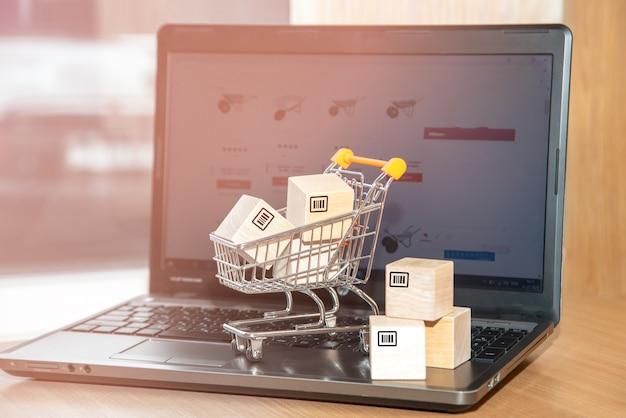 オンラインストア。ノートパソコンのキーボードにバーコードが付いた箱またはパッケージ。オンラインストアでは、商品の宅配を提供しています。