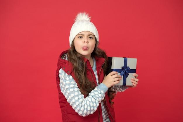 Online store. bully kid in winter outfit red background. new year is coming. small gift box for child. christmas gifts and souvenirs. prepare for winter holidays. make pleasant things.
