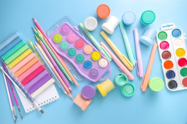 Онлайн учеба и рисование, дистанционно уроки живописи. различные красочные канцелярские товары и принадлежности для рисования. краски, пастель, карандаши, кисти, планшет на синем фоне. плоский вид сверху копией пространства
