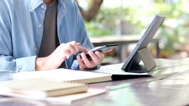 オンライン学習クラスeラーニングに携帯電話とデジタルタブレットを使用する男の手の学生