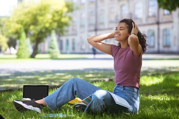 Онлайн-обучение. девушка в повседневной одежде сидит на траве в парке и учится