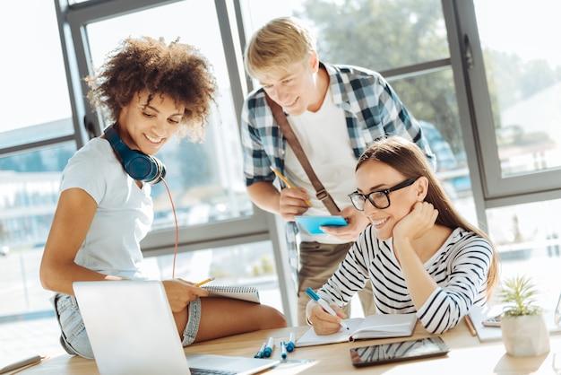 Онлайн-обучение. веселая молодая группа студентов, использующих свой ноутбук и делающих заметки во время совместной учебы