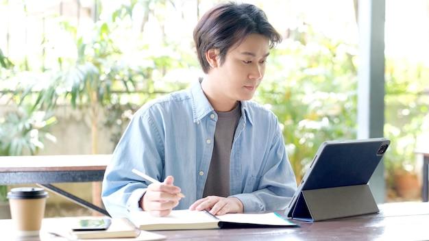 Eラーニングにデジタルタブレットを使用しながらノートに書くオンライン学習クラスの学生男性