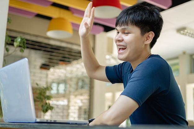 온라인 학습 개념 온라인 교실에서 공부하는 남학생은 왼손을 들어 교사에게 몇 가지 질문을 하는 새 흰색 노트북을 사용합니다.