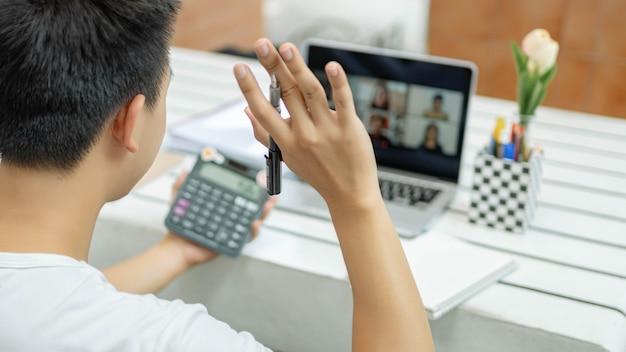 オンライン学習の概念無地の白いtシャツを着た男性は、非常に満足しており、会計クラスで数値を計算するための計算機を持っています。