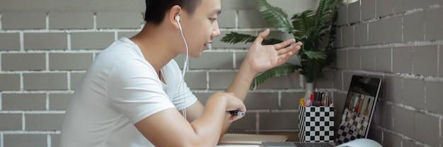 온라인 학습 개념 대학생이 그의 반 친구들이 그것을 듣고 있는 동안 노트북에 결론을 내리는 주제에 대한 자신의 의견을 설명하려고 합니다.