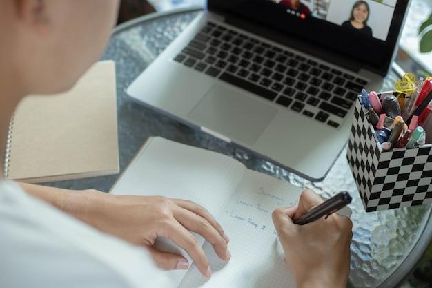 オンライン学習の概念大学生は、クラスメートがそれを聞いている間にノートブックで結論付けた主題に対する彼の意見を説明しようとしています。