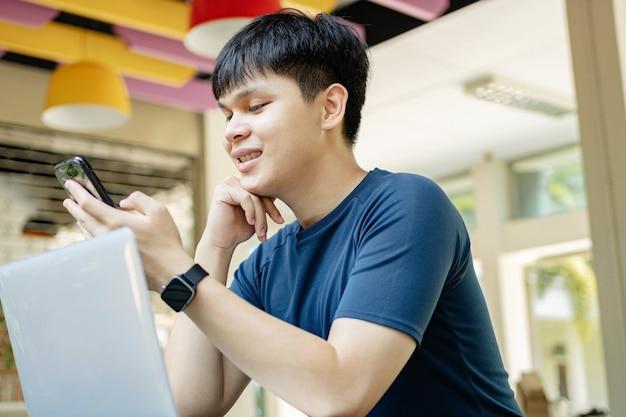 Концепция онлайн-обучения: молодой человек в темно-синей футболке и черных часах использует свой смартфон, чтобы позвонить своим друзьям, потому что они в данный момент не появляются на онлайн-встречах.