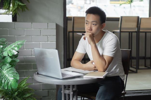 온라인 학습 개념 단순한 흰색 티셔츠를 입은 청년은 온라인 수업 중에 화면 앞에서 사려 깊고 진지합니다.